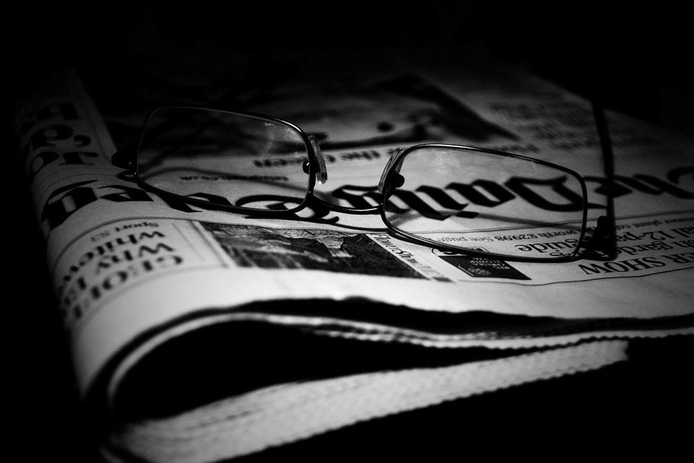 Brille auf einer Zeitung in dunkler Szenerie