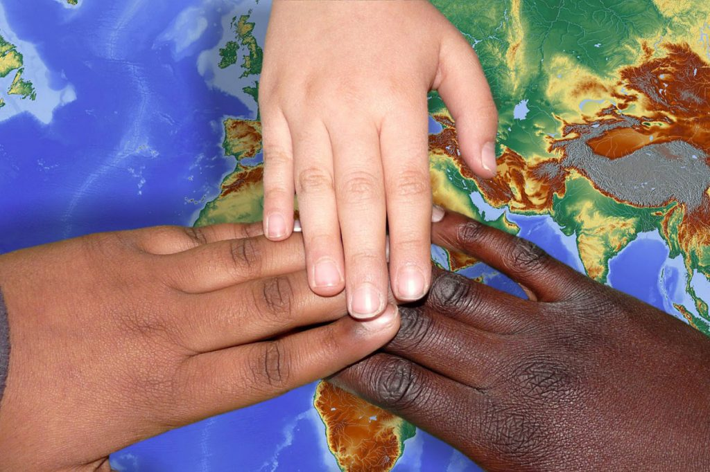 Hände unterschiedlicher Hautfarbe auf Weltkarte