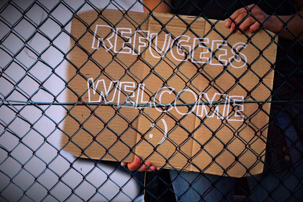 """Pappschild hinter einen Drahtzaun mit der Aufschrift """"Refugees Welcome"""""""