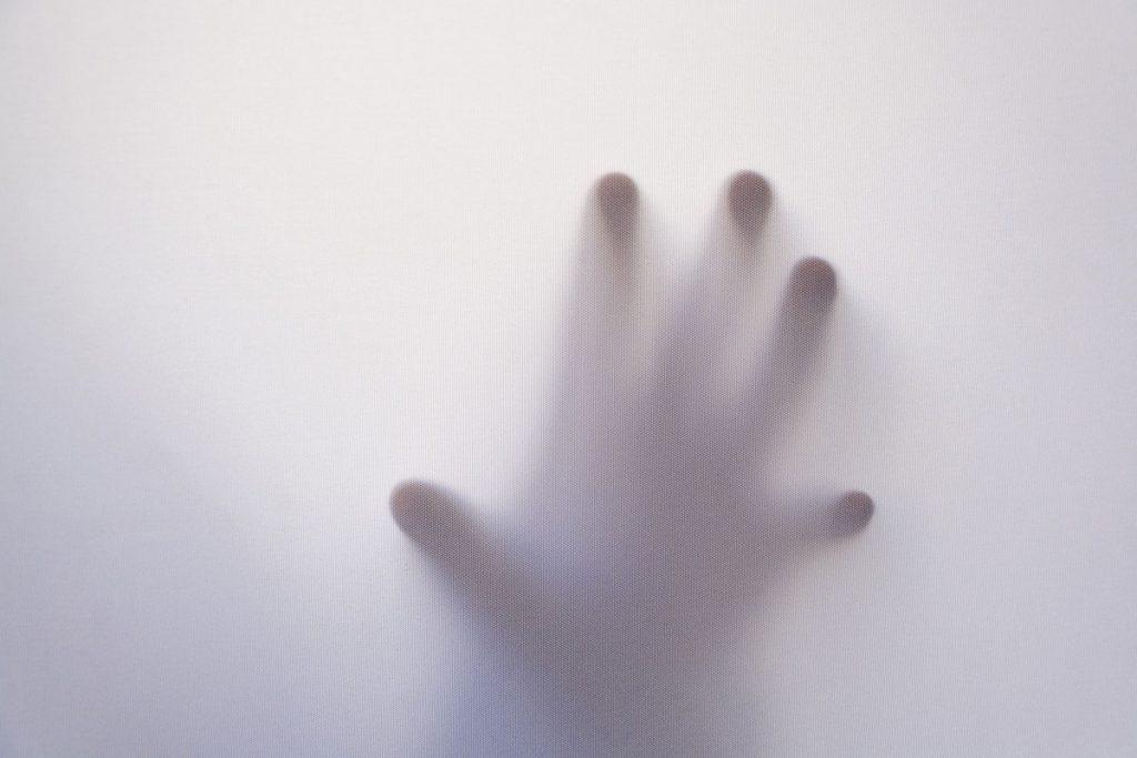 Konturen einer Hand hinter Milchglasscheibe