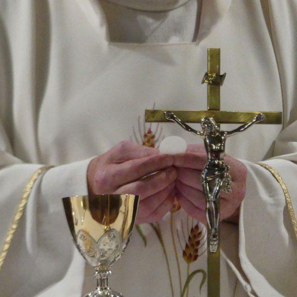 Priester mit Kelch und Kreuz im Vordergrund