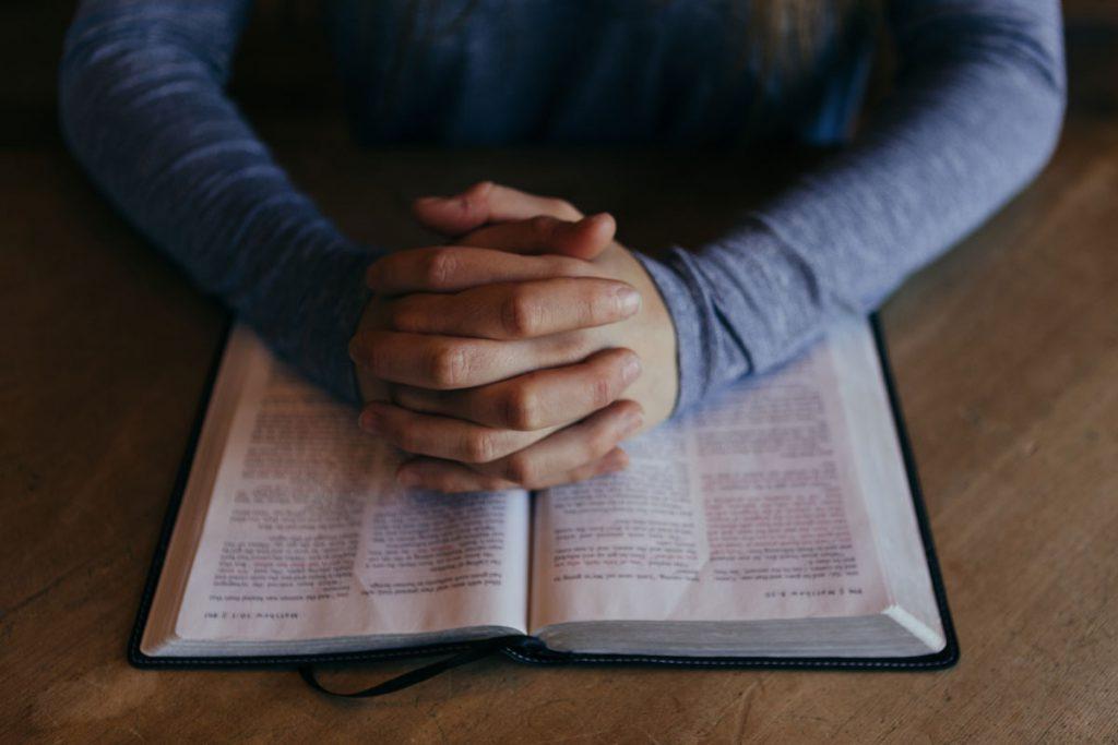 Gefaltete Hände auf der Bibel